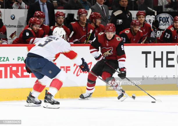 Clayton Keller of the Arizona Coyotes skates with the puck while being defended by Keith Yandle of the Florida Panthers at Gila River Arena on...