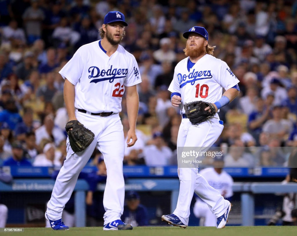 Clayton Kershaw #22 and Justin Turner #10 of the Los Angeles Dodgers react to a Kershaw throwing error allowing Gorkys Hernandez #66 of the San Francisco Giants to reach base during the fourth inning at Dodger Stadium on May 1, 2017 in Los Angeles, California.