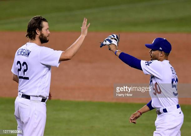 Clayton Kershaw and Mookie Betts celebrate a 3-0 win, to eliminate the Milwaukee Brewers after game two of the National League Wild Card Series at...