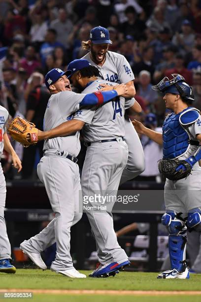 Clayton Kershaw of the Los Angeles Dodgers celebrates with relief pitcher Kenley Jansen and Yasmani Grandal after beating the Arizona Diamondbacks 31...