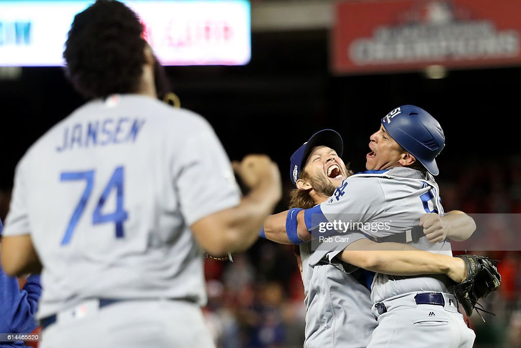 Clayton Kershaw #22 of the Los Angeles Dodgers celebrates with teammate Carlos Ruiz #51 after winning game five of the National League Division Series over the Washington Nationals 4-3 at Nationals Park on October 13, 2016 in Washington, DC.