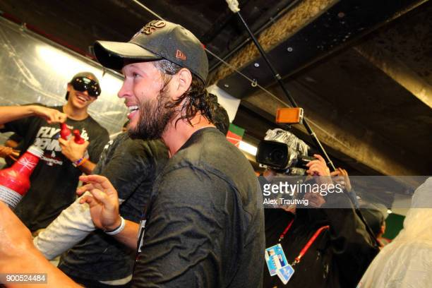 Clayton Kershaw of the Los Angeles Dodgers celebrates with teammates in the clubhouse after winning Game 5 of the National League Championship Series...