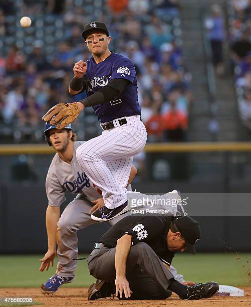 Clayton Kershaw of the Los Angeles Dodgers gets back to second base safely as shortstop Troy Tulowitzki of the Colorado Rockies throws to first to...