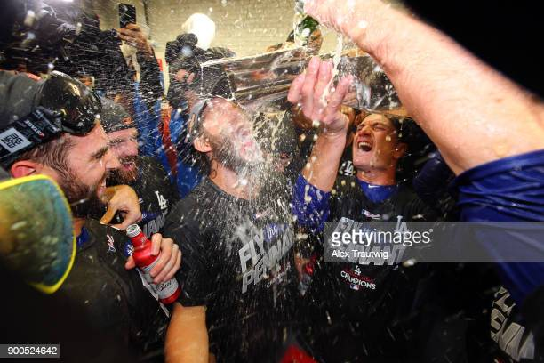 Clayton Kershaw of the Los Angeles Dodgers is doused with champagne by teammates in the clubhouse after winning Game 5 of the National League...