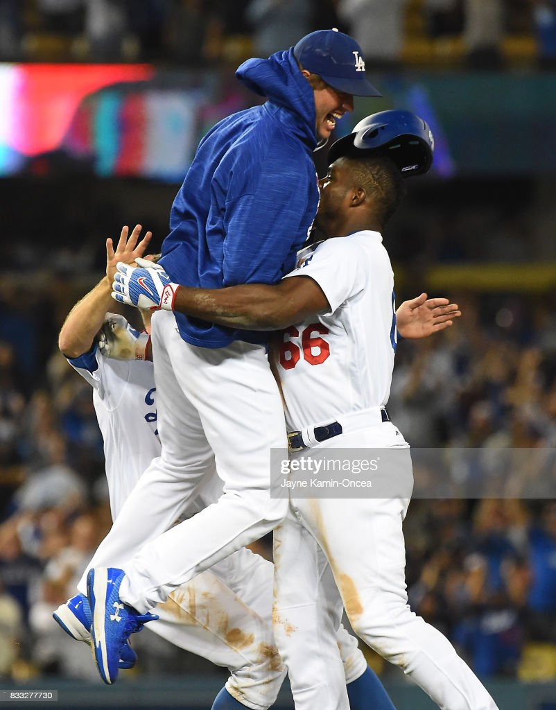 Clayton Kershaw #22 of the Los Angeles Dodgers leaps into the arms of Yasiel Puig #66 of the Los Angeles Dodgers after Puig hit a walk off three-run home run to defeat the Chicago White Sox in the ninth inning of the game at Dodger Stadium on August 16, 2017 in Los Angeles, California.