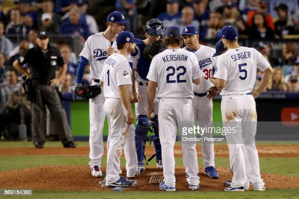 Clayton Kershaw of the Los Angeles Dodgers meets with teammates and manager Dave Roberts on the pitcher's mound during the sixth inning against the...