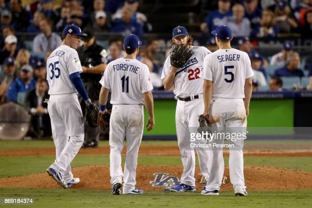 Clayton Kershaw of the Los Angeles Dodgers meets with teammates on the pitcher's mound during the sixth inning against the Houston Astros in game...