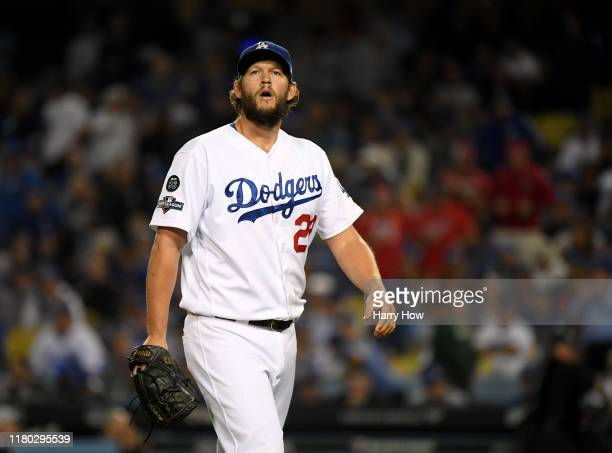 Clayton Kershaw of the Los Angeles Dodgers reacts as he leaves the game after giving up back to back home runs in the eighth inning of game five of...