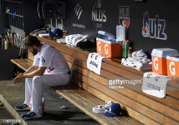 Clayton Kershaw of the Los Angeles Dodgers sits in the dug out after leaving the game after giving up back to back home runs in the eighth inning of...