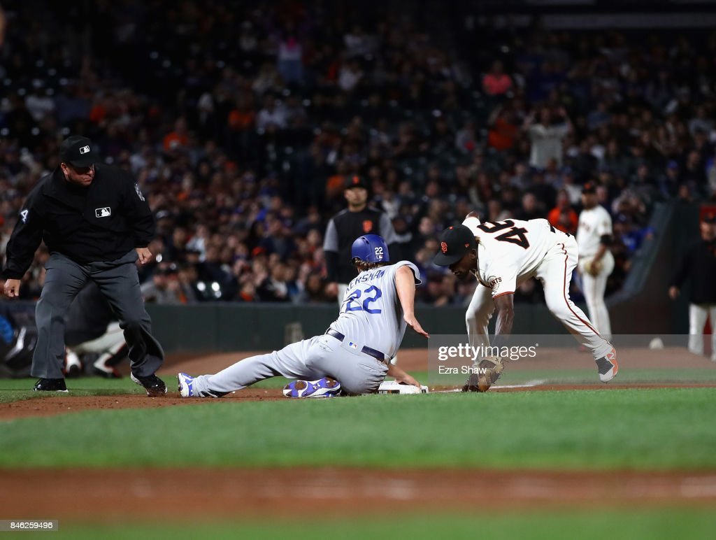 Clayton Kershaw #22 of the Los Angeles Dodgers slides safely past Orlando Calixte #46 of the San Francisco Giants at third base on a ball hit by Chris Taylor #3 in the fourth inning at AT&T Park on September 12, 2017 in San Francisco, California.