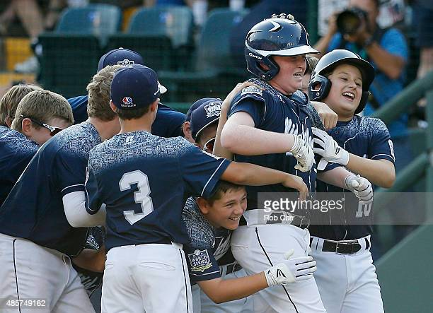 Clayton Krauss of the MidAtlantic team from Red Land Little League of Lewisberry Pennsylvania celebrates with teammates after hitting a walk off...
