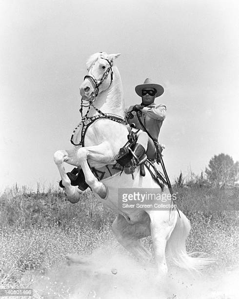 Clayton Moore US actor in costume as he sits on his horse 'Silver' which rears up in a publicity still issued for the television series 'The Lone...