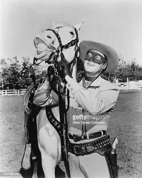 Clayton Moore US actor in costume holding the reigns of his horse Silver in a publicity still issued for the television series 'The Lone Ranger' USA...