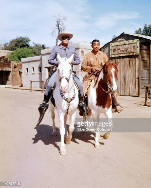 Clayton Moore US actor in costume riding his horse 'Silver' alongside Jay Silverheels Canadian Mohawk actor in costume on his horse 'Scout' in a...