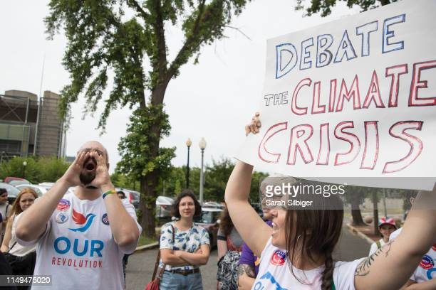 Clayton Northcraft and Suzannah Mullen shout in front of the Democratic National Committee headquarters during a Greenpeace rally to call for a...