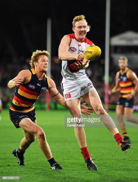 Clayton Oliver of the Demons handballs as Rory Sloane of the Crows attempts to tackle during the round eight AFL match between the Adelaide Crows and...