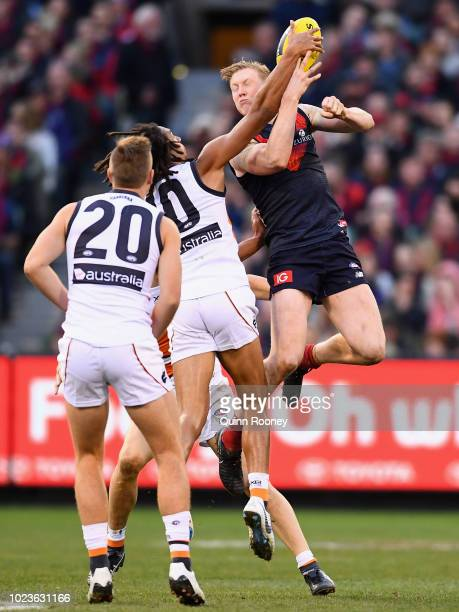 Clayton Oliver of the Demons handballs whilst being tackled by Aiden Bonar of the Giants during the round 23 AFL match between the Melbourne Demons...