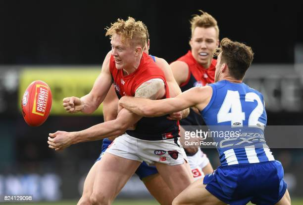 Clayton Oliver of the Demons handballs whilst being tackled by Declan Mountford of the Kangaroos during the round 19 AFL match between the North...