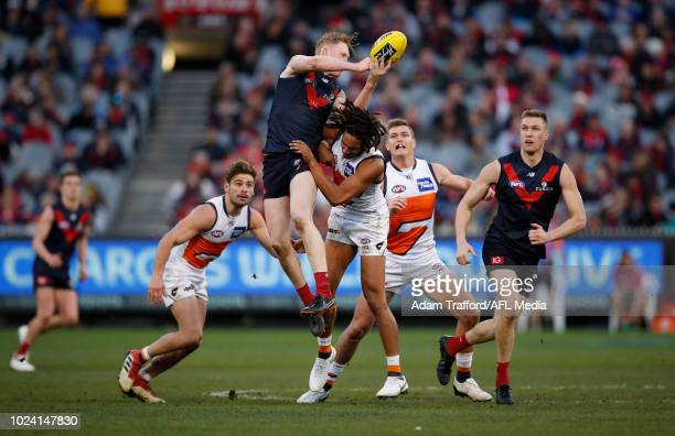 Clayton Oliver of the Demons handpasses the ball while being tackled by Aiden Bonar of the Giants during the 2018 AFL round 23 match between the...