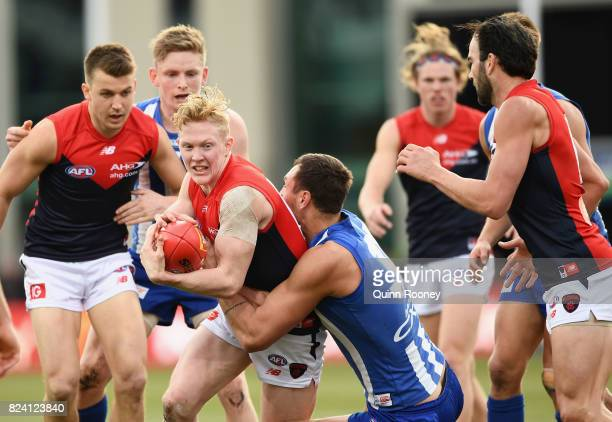 Clayton Oliver of the Demons is tackled by Braydon Preuss of the Kangaroos during the round 19 AFL match between the North Melbourne Kangaroos and...