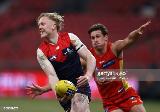 Clayton Oliver of the Demons runs clear of David Swallow of the Suns during the round 6 AFL match between the Melbourne Demons and the Gold Coast...