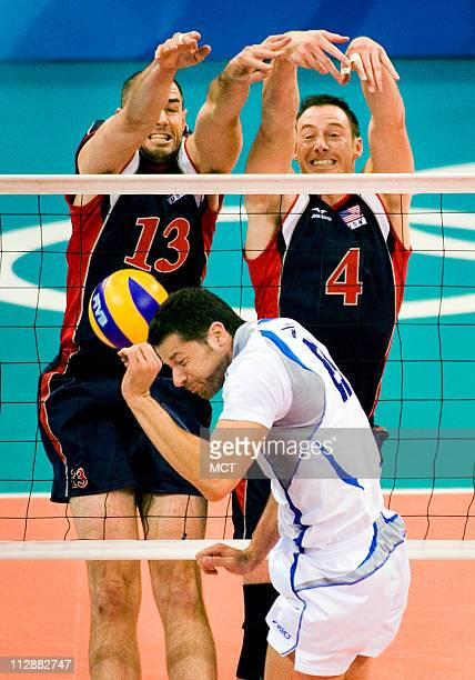 Clayton Stanley and David Lee of the United States block a shot on Italy's Alberto Cisolla in a volleyball match on Tuesday August 12 in the Games of...