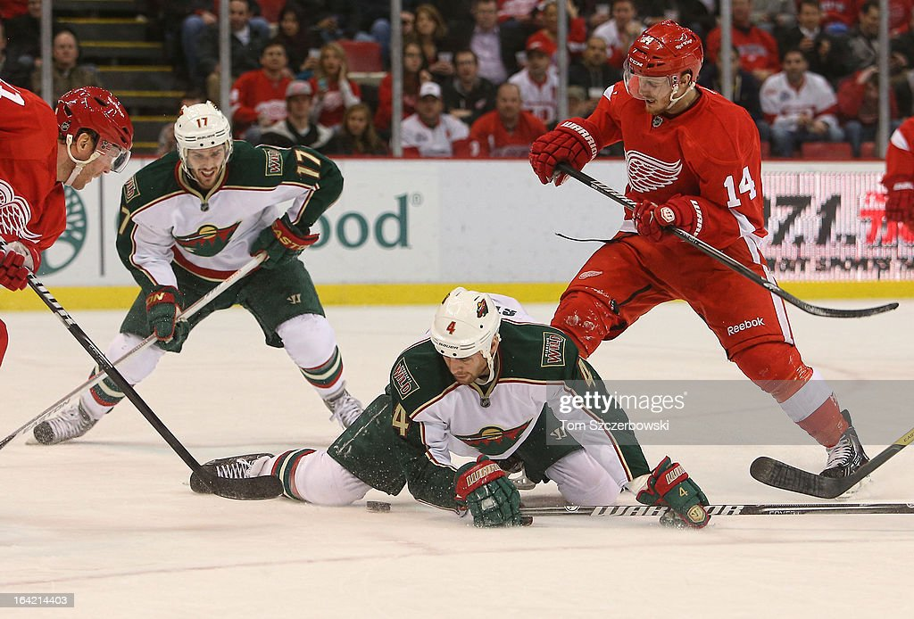 Clayton Stoner #4 of the Minnesota Wild falls on the puck as Patrick Eaves #14 of the Detroit Red Wings bears down in NHL action at Joe Louis Arena on March 20, 2013 in Detroit, Michigan.
