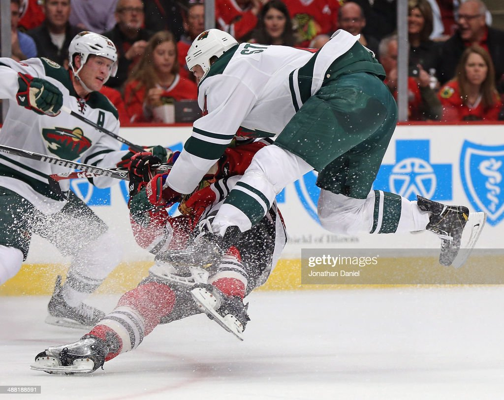 Clayton Stoner #4 of the Minnesota Wild takes to the air to knock down Ben Smith #28 of the Chicago Blackhawks in Game Two of the Second Round of the 2014 NHL Stanley Cup Playoffs at the United Center on May 4, 2014 in Chicago, Illinois.