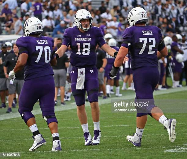 Clayton Thorson of the Northwestern Wildcats congratulates teammates Rashawn Slater and Blake Hance after scoring a touchdown on a quarterback sneak...