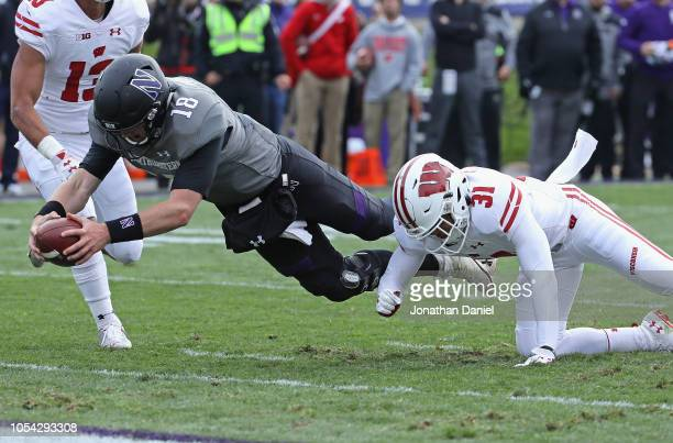 Clayton Thorson of the Northwestern Wildcats dives into the end zone past Madison Cone of the Wisconsin Badgers to score a touchdown at Ryan Field on...