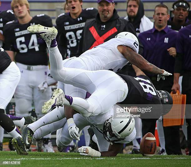 Clayton Thorson of the Northwestern Wildcats fumbles as he is hit by Marcus Allen and Jason Cabinda of the Penn State Nittany Lions at Ryan Field on...