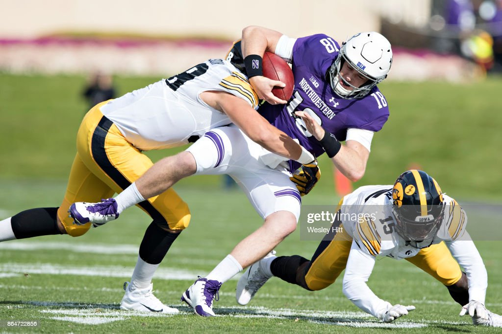 Clayton Thorson #18 of the Northwestern Wildcats is tackled by Anthony Nelson #98 of the Iowa Hawkeyes at Ryan Field on October 21, 2017 in Evanston, Illinois. The Wildcats defeated the Hawkeyes 17-10.