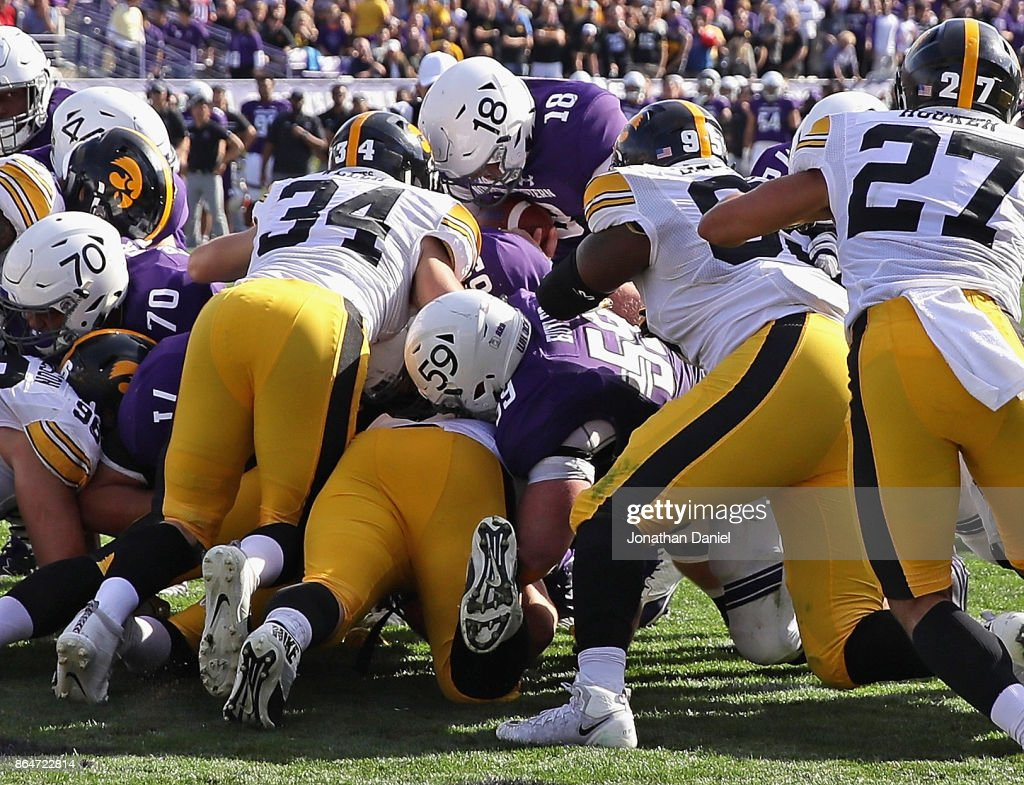 Clayton Thorson #18 of the Northwestern Wildcats scores the game-winning touchdown in overtime against the Iowa Hawkeyes at Ryan Field on October 21, 2017 in Evanston, Illinois. Northwestern defeated Iowa 17-10 in overtime.