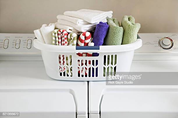 Clean Folded Towels in Laundry Basket on Top of Washer and Dryer