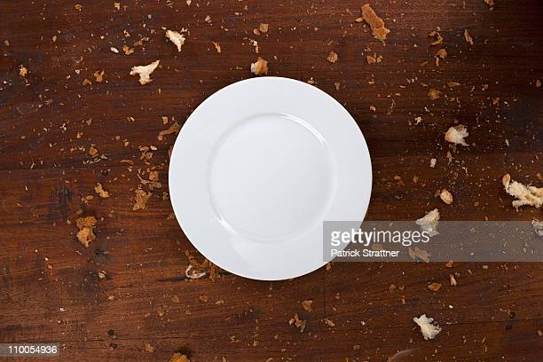 A clean plate on a table with crumbs