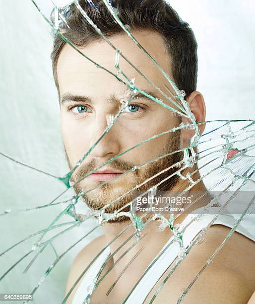 Clean portrait of a young man in a broken mirror