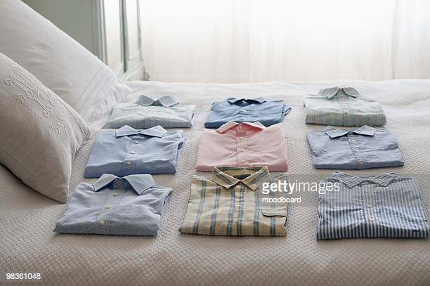 Clean shirts ordered on a bed