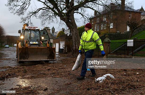 Clean up crews begin to clear up the debris left in the residential streets after the river Tweed burst it's banks flooding the area on December 31...