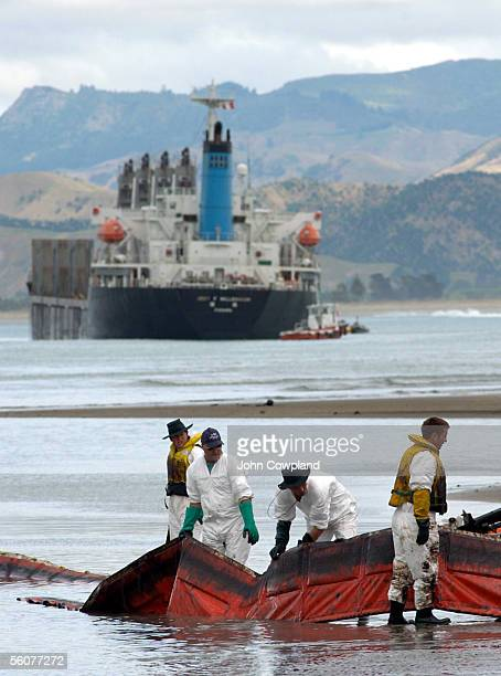 Clean up crews remove a spill containment boom from the river mouth as the ship Jody F Millennium that is aground and is leaking oil and fuel off the...