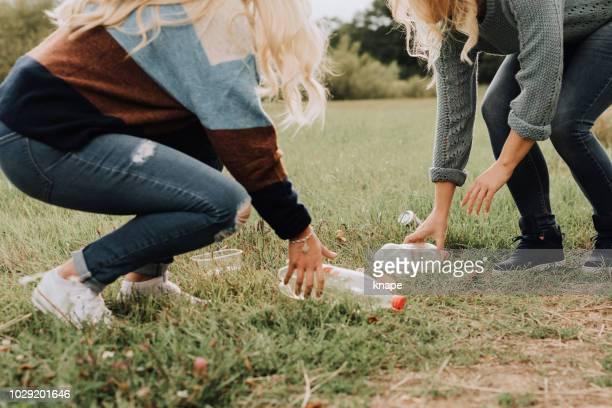 clean up vrouwen oppakken van plastic afval en pet flessen in de natuur - oppakken stockfoto's en -beelden