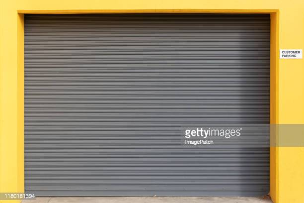 clean vehicle roller door set in bright yellow surround - industrial door stock pictures, royalty-free photos & images