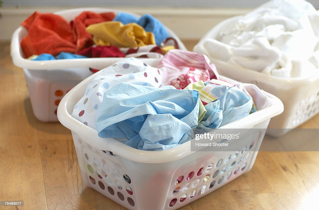 Clean washing in three plastic laundry baskets : Stock Photo