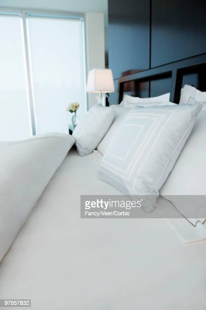 Clean white bed linens on bed