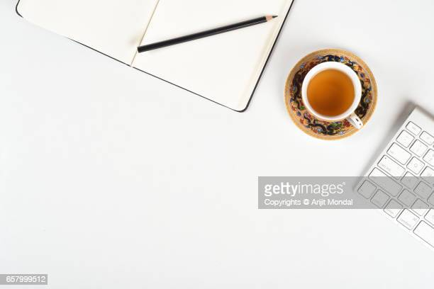 clean white office desk of a professional with writing notebook, pencil, black tea and computer keyboard - website template stock photos and pictures