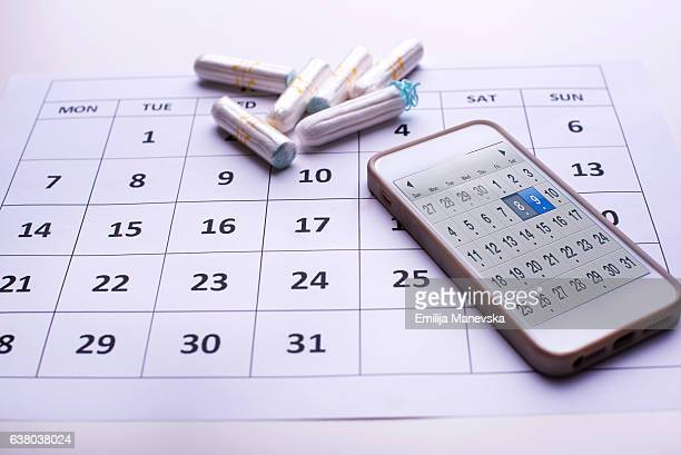 clean white tampons, mobile phone and calendar - weiblichkeit stock-fotos und bilder