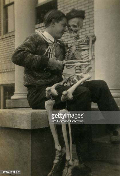 A cleancut college student sits on a stoop posing with a skeleton in his lap circa 1927