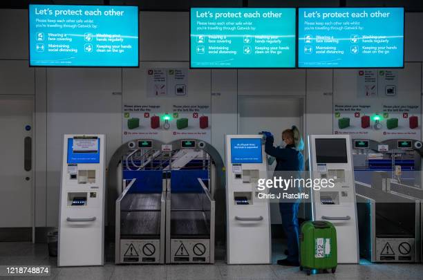 A cleaner disinfects self check in machines as a protective measure against the spread of Covid19 inside the currently closed North Terminal at...