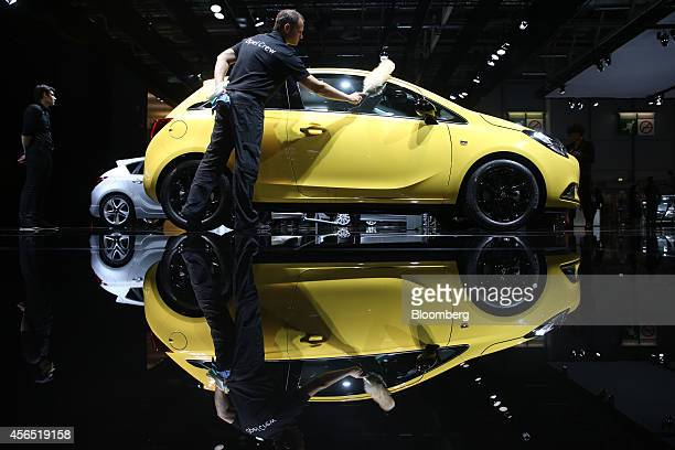 A cleaner dusts an Opel Corsa automobile following its unveiling at the Adam Opel AG stand on the first preview day at the Paris Motor Show in Paris...