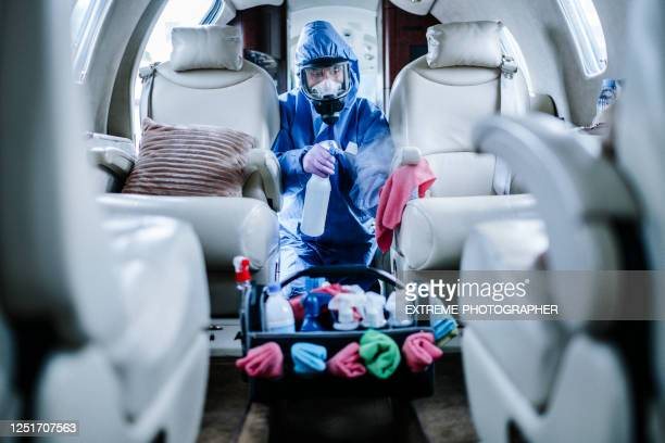 a cleaner in blue coveralls disinfecting the passenger cabin before flight - department of health stock pictures, royalty-free photos & images