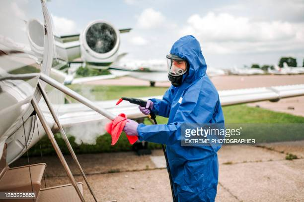 a cleaner in coveralls wiping down the handrail of boarding stairs on a small private plane parked on an airport tarmac during the covid-19 pandemic - department of health stock pictures, royalty-free photos & images